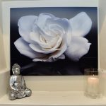 A silver buddha string on a shelf under a picture on the wall of a gardenia in white